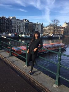 Maria Amupolo on her travels through Europe, standing at one of Amsterdam's canals.